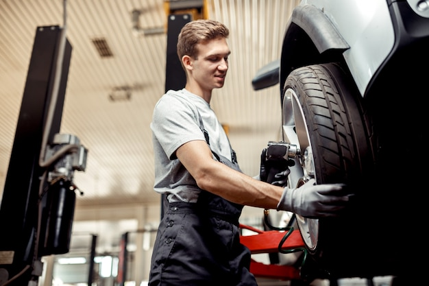 Um mecânico de automóveis troca um pneu enquanto trabalha em uma oficina mecânica.