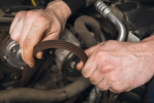 Um mecânico de automóveis verifica a condição da correia do alternador durante uma inspeção técnica