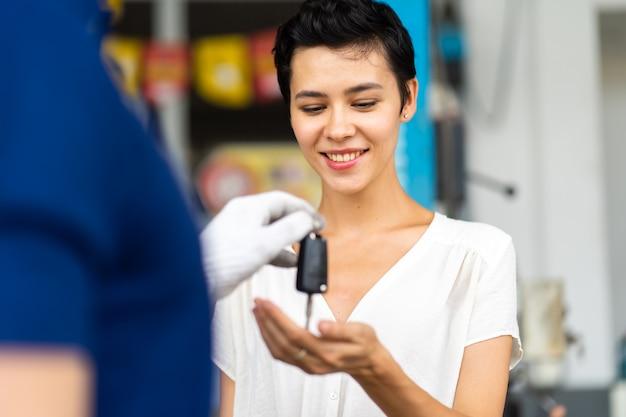 Um mecânico de meia-idade com barba dá a chave do carro para uma cliente na estação de manutenção de automóveis e na oficina de automóveis