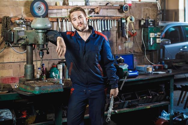 Um mecânico em um traje de proteção azul está de pé em uma garagem de carro perto de uma furadeira