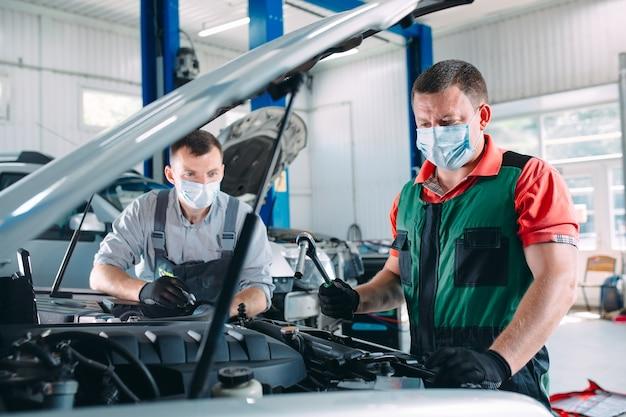 Um mecânico mascarado verifica o carro na estação de serviço