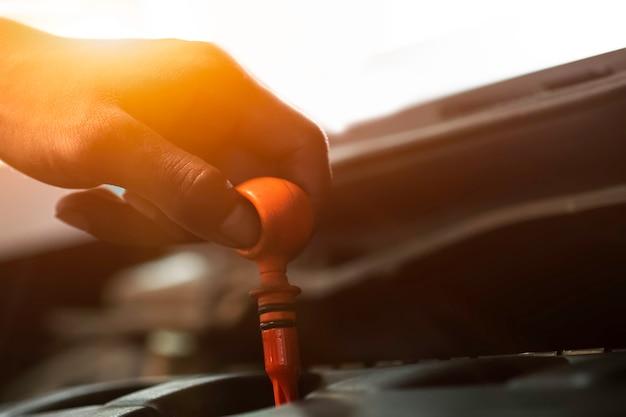 Um mecânico na garagem verifique o óleo. equipamentos de trabalho como luvas.