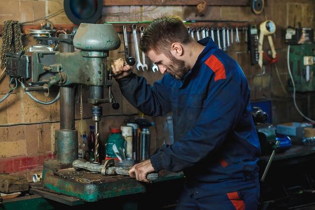 Um mecânico perfura um detalhe em uma prensa de broca. mecânico de fluxo de trabalho em uma garagem de carro.