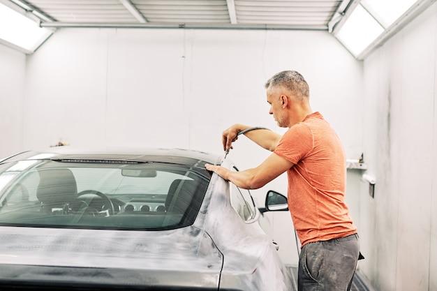 Um mecânico preparando um carro para pintá-lo