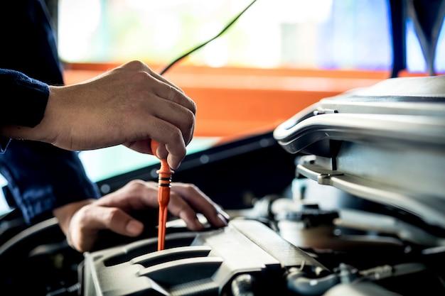 Um mecânico verifique o óleo. equipamentos de trabalho como luva