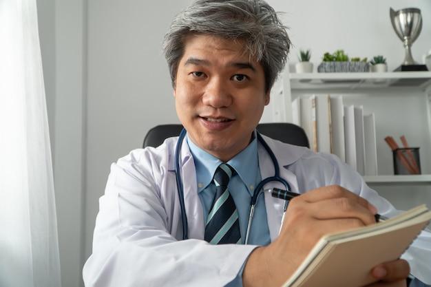 Um médico asiático está online visitando um paciente na internet e anota os sintomas
