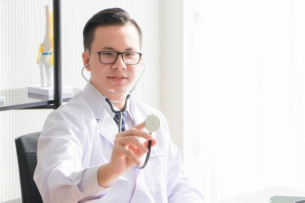 Um médico asiático, tailandês, usa óculos e uniforme. o médico está sentado, segurando e segurando o estetoscópio na sala de exame