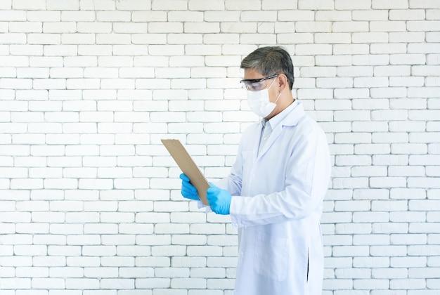 Um médico asiático usa óculos transparentes e uma máscara facial segurando uma ficha médica em um hospital.