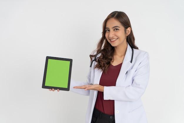 Um médico atraente sorri com um gesto oferecendo algo enquanto mostra a tela de um bloco para t ...