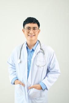 Um médico bonito com um estetoscópio de pé confiante na parede branca