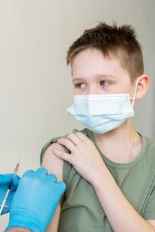 Um médico com máscara protetora e estetoscópio vacina uma criança