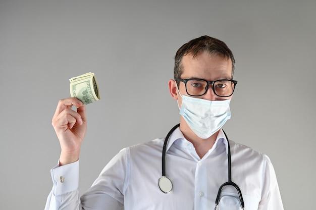 Um médico com máscara segura dinheiro na mão