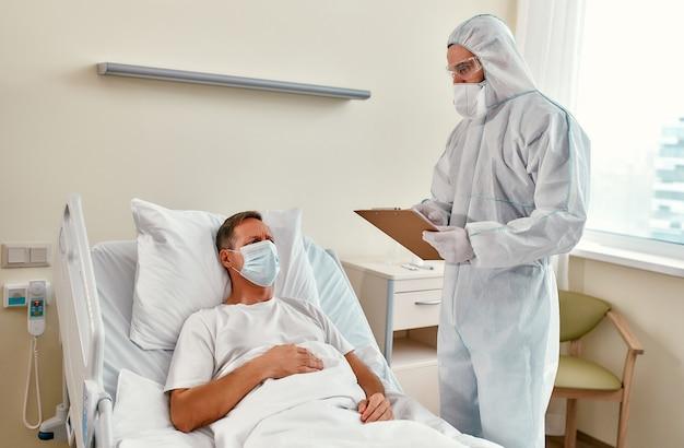 Um médico com roupa de proteção, respirador e óculos de proteção examina um paciente maduro que está deitado em uma enfermaria de hospital moderno durante a epidemia de coronavírus ou covid-19.