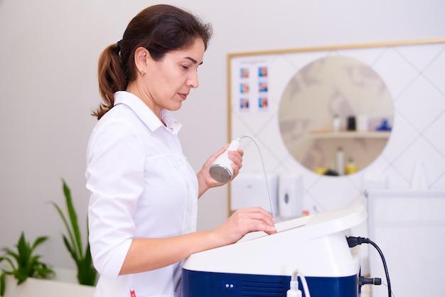 Um médico com um aparelho de cavitação em uma clínica de cosmetologia.