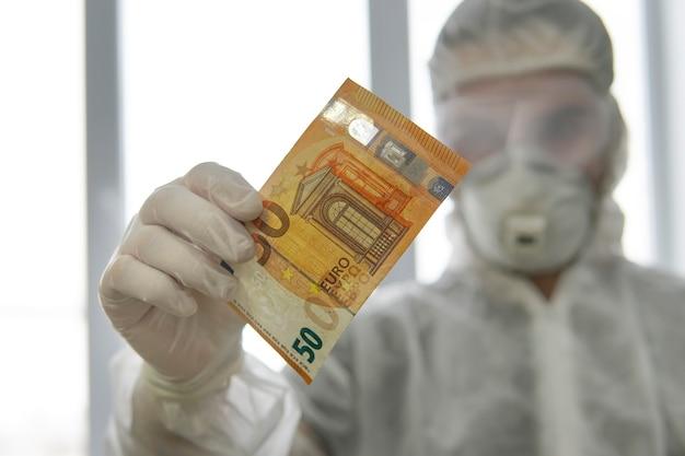 Um médico com uniforme de proteção tem notas de dinheiro nas mãos. pagamento pelo trabalho do médico. o perigo de germes em dinheiro. desinfecção de papel-moeda.