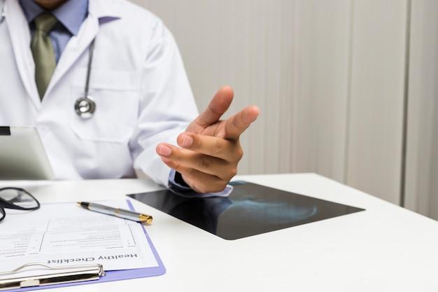 Um médico consulta paciente enquanto está sentado à mesa no escritório.