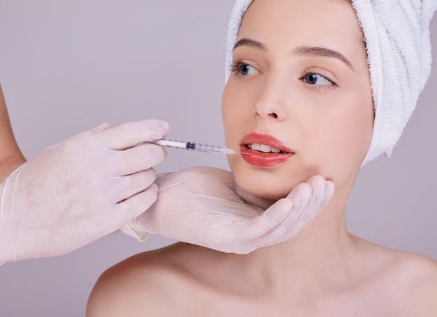 Um médico cosmetologista faz uma injeção nos lábios de uma jovem mulher.