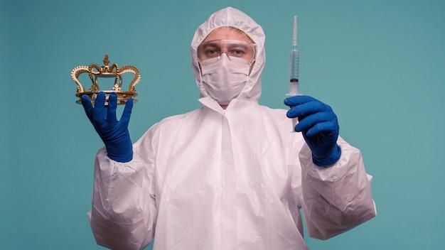 Um médico de macacão de proteção e máscara segura uma seringa com uma vacina e uma coroa nas mãos