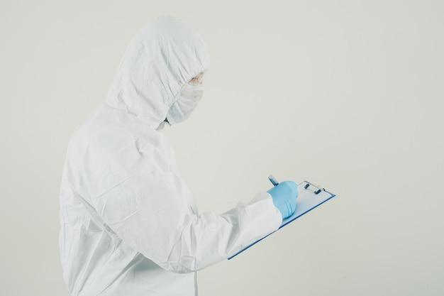 Um médico de pé e escrevendo o relatório médico