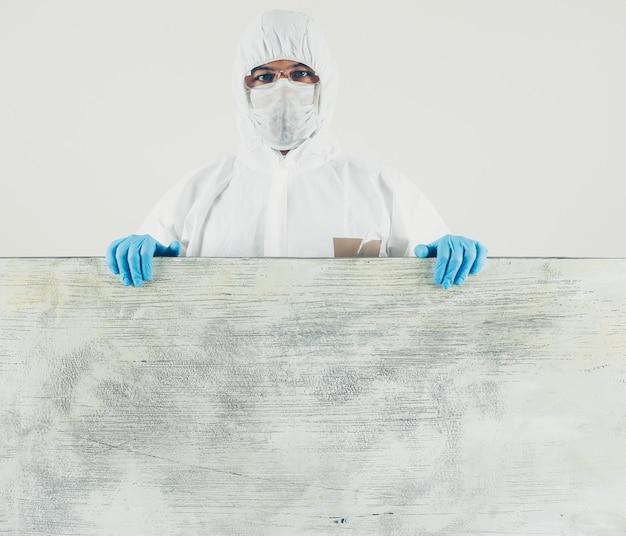 Um médico de pé na placa branca e de madeira com máscara, luvas e traje de proteção