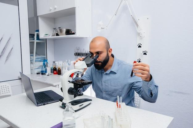 Um médico do sexo masculino estuda vírus e bactérias em um microscópio. pesquisa de vírus e bactérias perigosos.