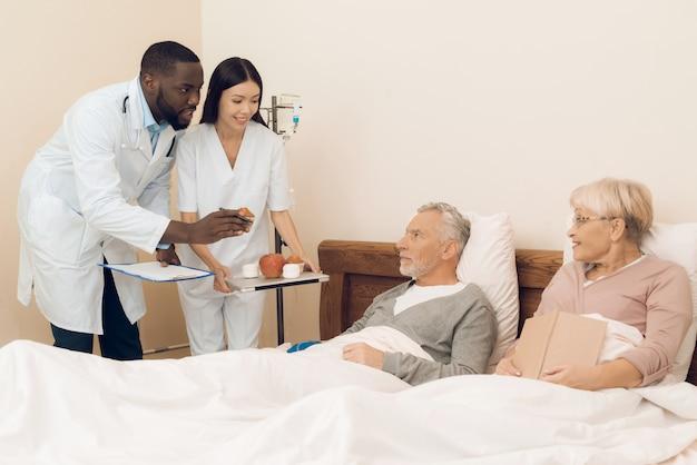 Um médico e uma enfermeira oferecem um casal de idosos uma maçã