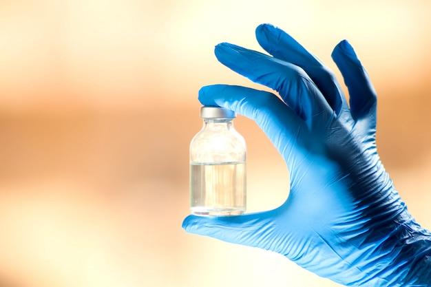 Um médico em luvas azuis, segurando uma garrafa com vacina. feche acima do tiro. conceito de medicina e saúde
