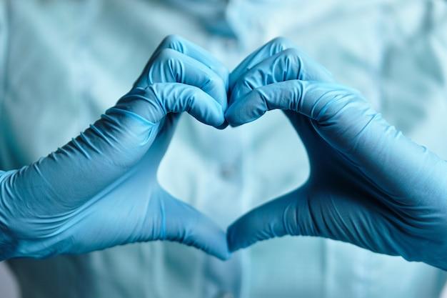 Um médico em luvas médicas azuis faz um coração com as mãos.