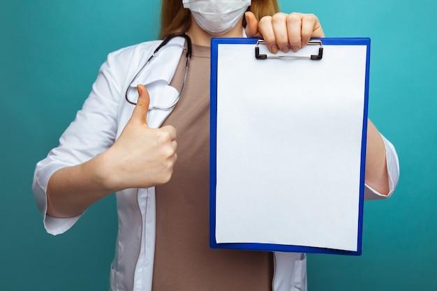 Um médico em máscara facial de vestido médico isolada em azul. segure a área de transferência com o espaço de trabalho de folha vazia em branco.
