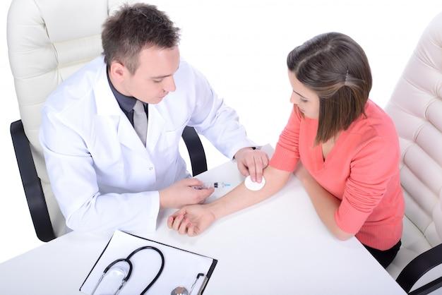 Um médico em um jaleco verifica uma menina.