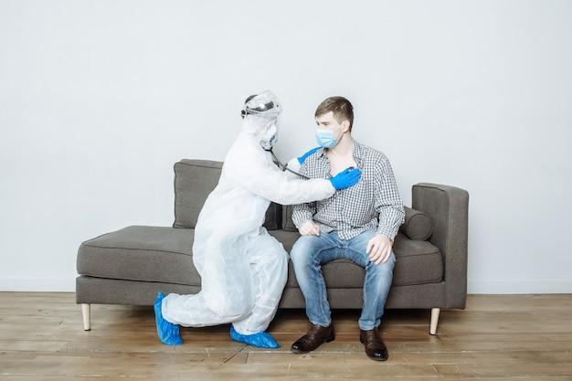 Um médico em um traje de proteção de material anti-risco de epi com uma máscara e luvas examina o paciente e escuta com um estetoscópio a respiração