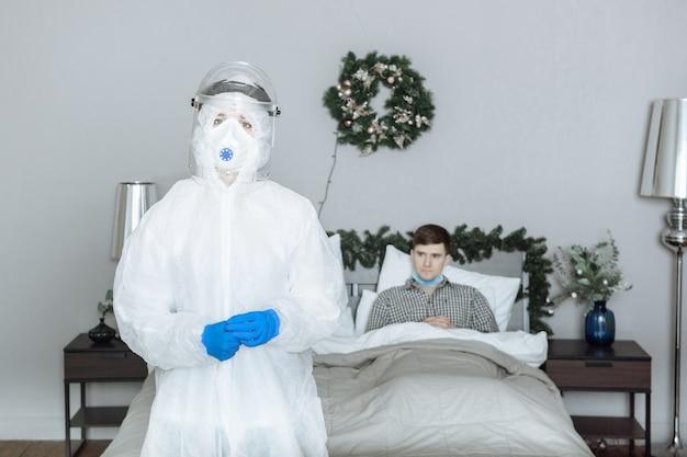 Um médico em um traje de proteção individual de material anti-risco de epi olha para a câmera