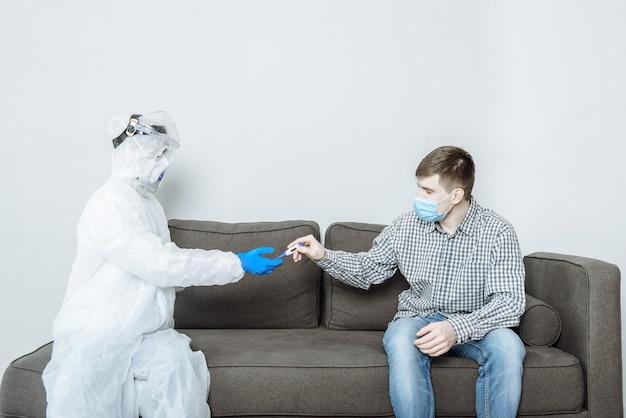Um médico em um traje de proteção ppe hazmat usando uma máscara e óculos dá um termômetro para um paciente