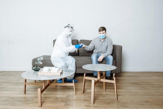 Um médico em uma roupa de proteção mede o nível de oxigênio de um paciente com um oxímetro de pulso para sintomas do coronavírus covid-19