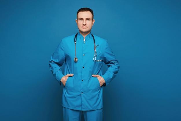 Um médico em uniforme médico, olhando para a câmera e posando no fundo azul jovem docto ...