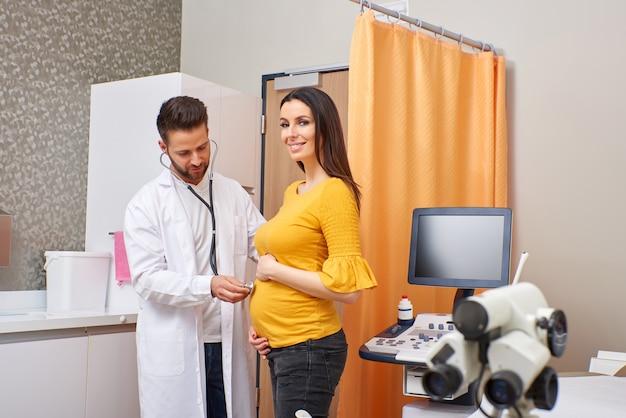 Um médico examinando uma mulher grávida
