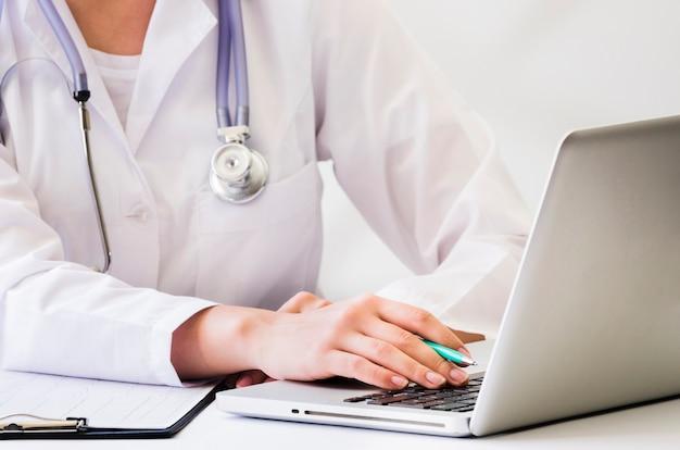 Um, médico feminino, com, estetoscópio, ao redor, dela, pescoço, usando computador portátil, escrivaninha