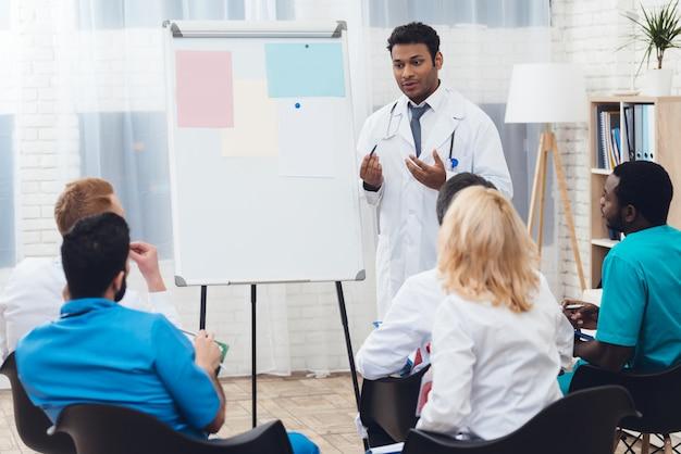 Um médico indiano aconselha colegas durante a reunião médica.