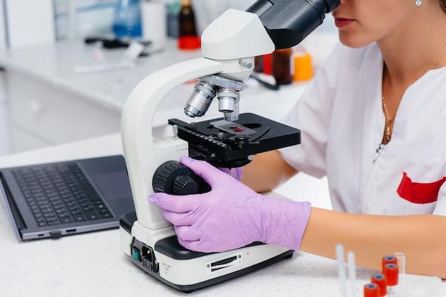 Um médico infectologista trabalha em um microscópio de close-up. estudo de vírus e bactérias no laboratório médico.