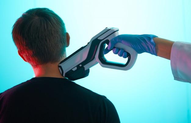 Um médico inocula um paciente do sexo masculino com uma pistola de injeção, no pescoço, close-up