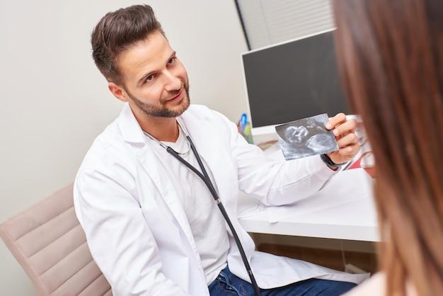 Um médico mostra o ultra-som para a mulher grávida