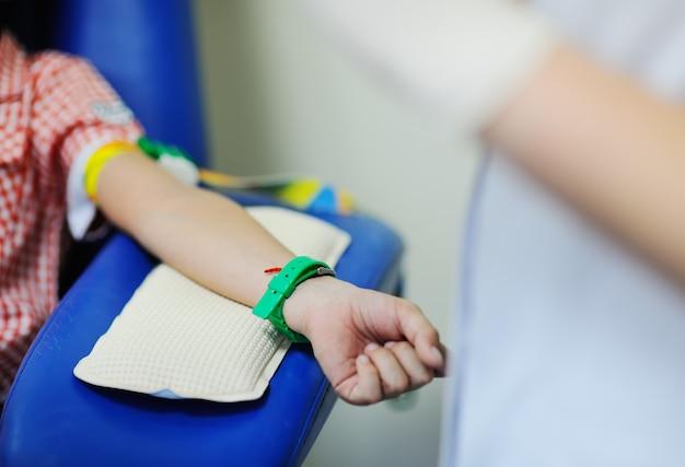 Um médico ou enfermeiro leva sangue de uma veia em uma criança de um menino