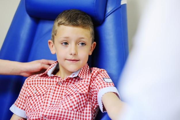 Um médico ou enfermeiro tira sangue da veia de um filho de menino. química do sangue