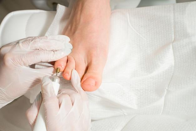 Um médico podólogo que cuida dos procedimentos cosméticos das unhas dos pés de uma mulher