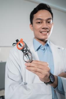 Um médico posa segurando uma armação de medidor de óculos em uma clínica de oftalmologia onde trabalha