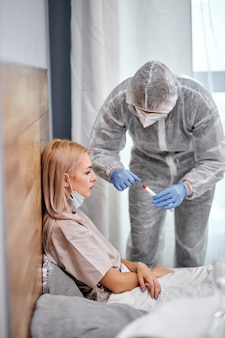 Um médico profissional vai colher esfregaço nasal de uma mulher doente, fazer um teste para paciente jovem covid-19 na visita domiciliar. médico protegido com luvas e traje de proteção individual. teste rápido de antígeno durante a pandemia de coronavírus
