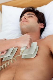 Um médico realizando uma rcp com um desfibrilador