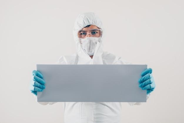 Um médico segurando o cartão branco em luvas médicas e traje de proteção em fundo claro. espaço para coronavírus de texto