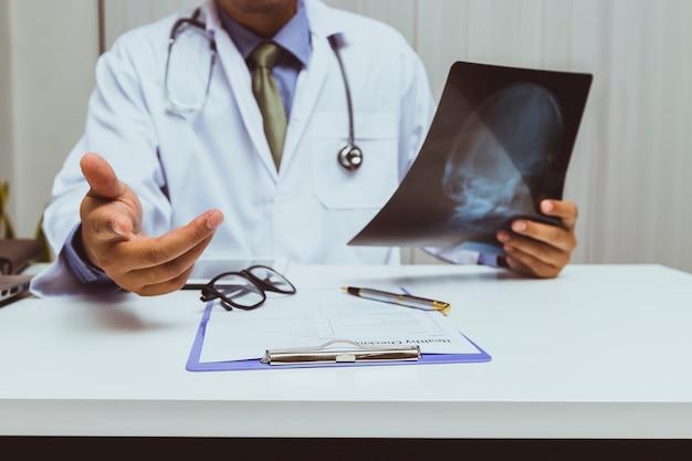 Um médico segurando o filme de raio-x e consulta paciente no escritório.
