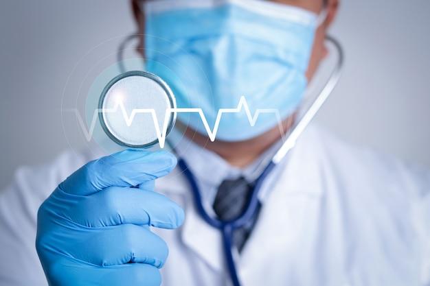 Um médico usando uma máscara azul segura um estetoscópio para examinar o paciente com um gráfico do ritmo das ondas cardíacas.